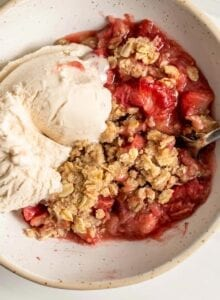 A bowl of strawberry rhubarb crisp with vanilla ice cream and a spoon in it.