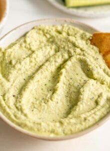A bowl of green hummus with some chopped cucumber and pita chips.