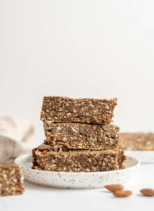 3 raw energy bars stacked on a small round plate with some almonds in the foreground.