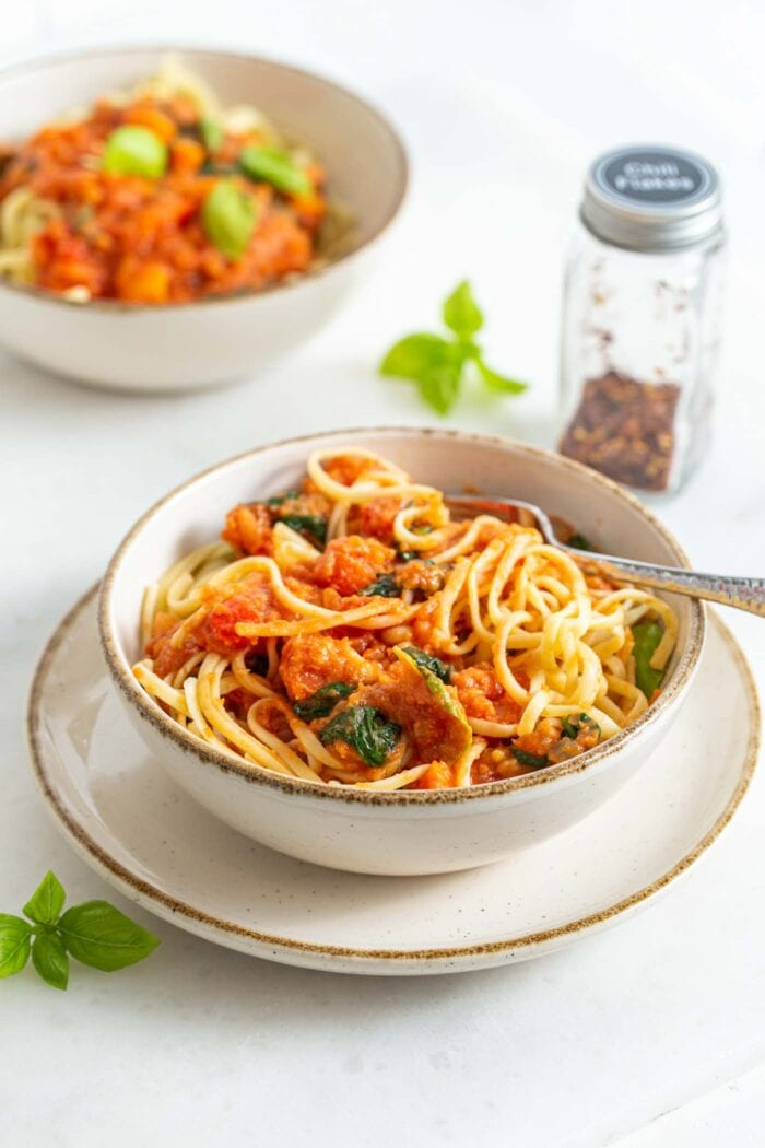 A bowl of spaghetti mixed with tomato sauce and fresh basil.