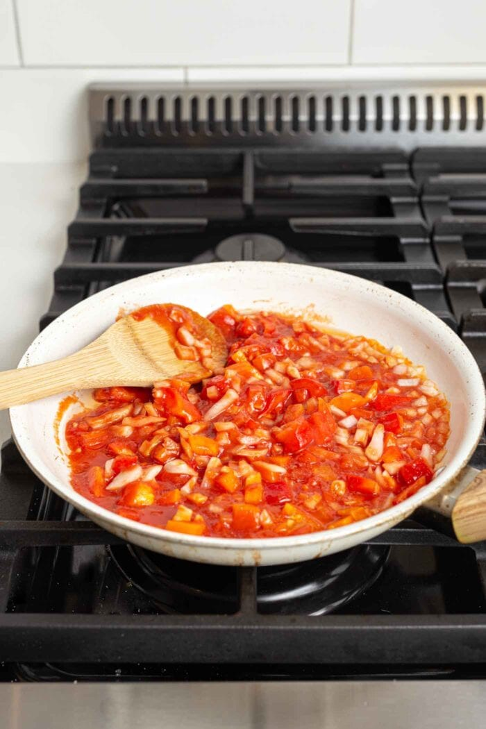 Chunky vegetable pasta sauce cooking in a skillet on a gas cooktop.