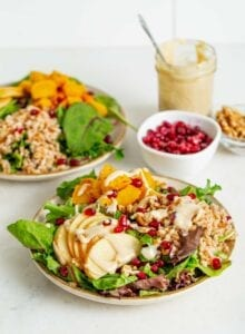 Two bowls of salad with apple, pomegranate, tahini sauce and walnuts.