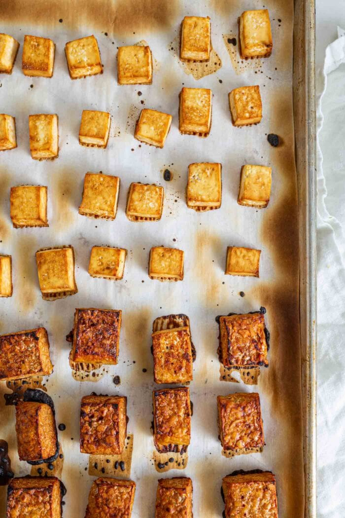 Cubed and baked tofu and tempeh on a baking pan.