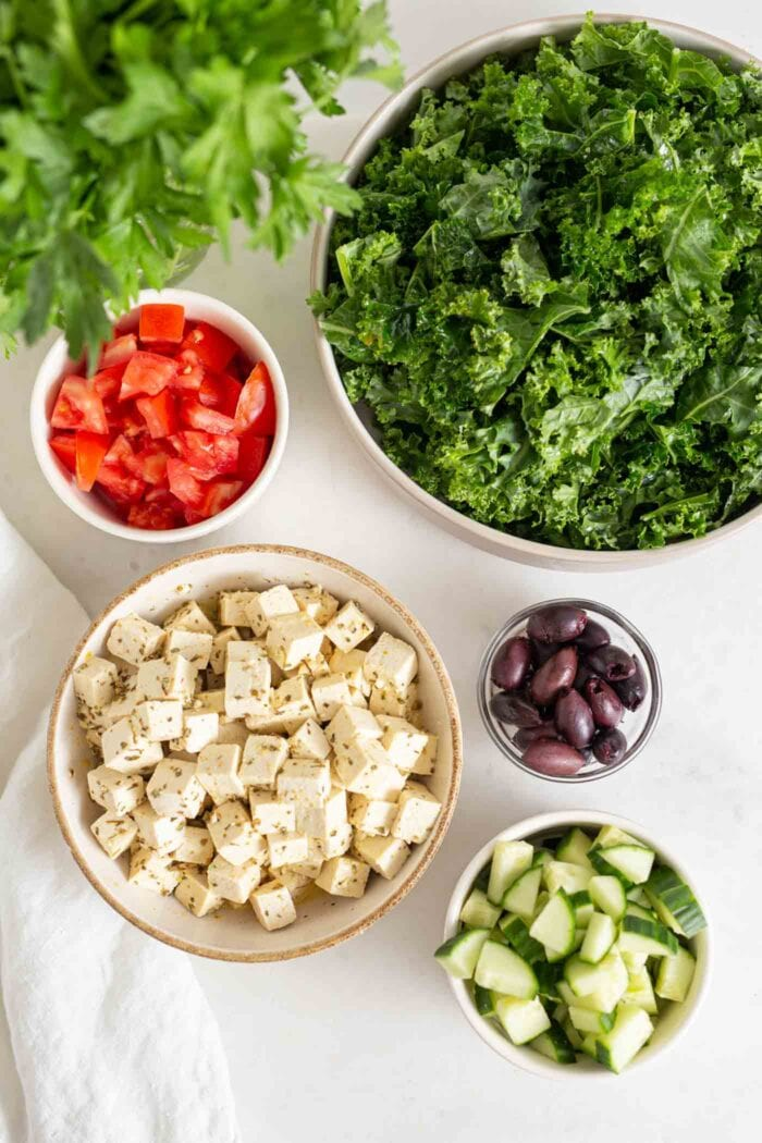 Tofu, olives, chopped kale, cucumber and tomato in bowls.