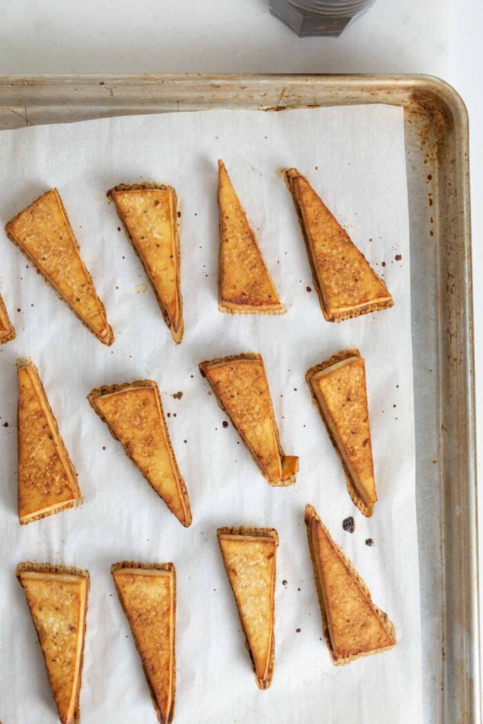 Browned triangles of tofu on a parchment paper-lined baking tray.