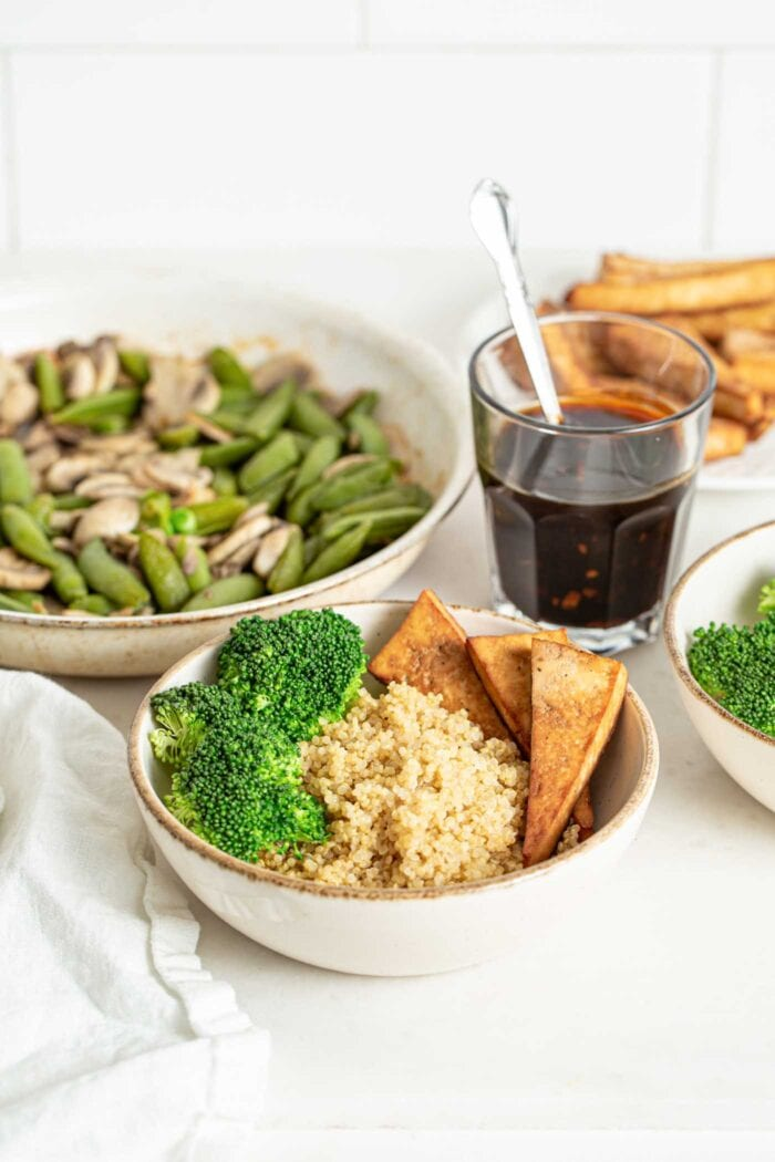 Quinoa, broccoli and tofu in a bowl, glass of sauce and skillet of mushrooms and snap peas in the background.