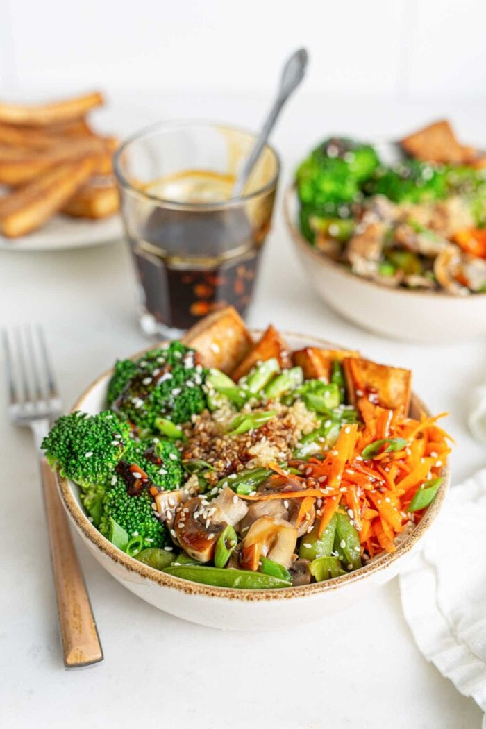 Bowl of quinoa, carrots, peas and mushrooms with teriyaki sauce. Sauce and another bowl in the background.