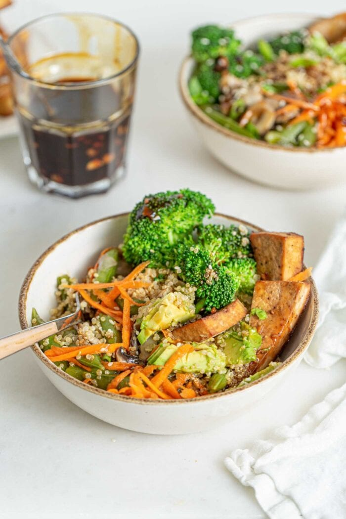 Quinoa, carrot, broccoli and tofu mixed up in a bowl with a fork.