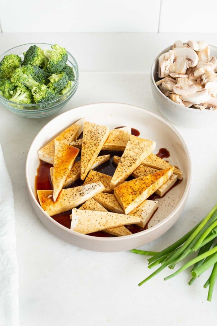 Tofu cut into triangles in a bowl with soy sauce, salt and pepper.