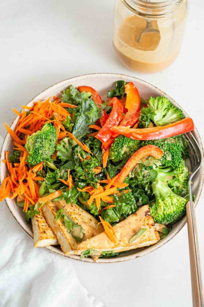 Overhead shot of a salad with tofu, kale, bell peppers and broccoli.