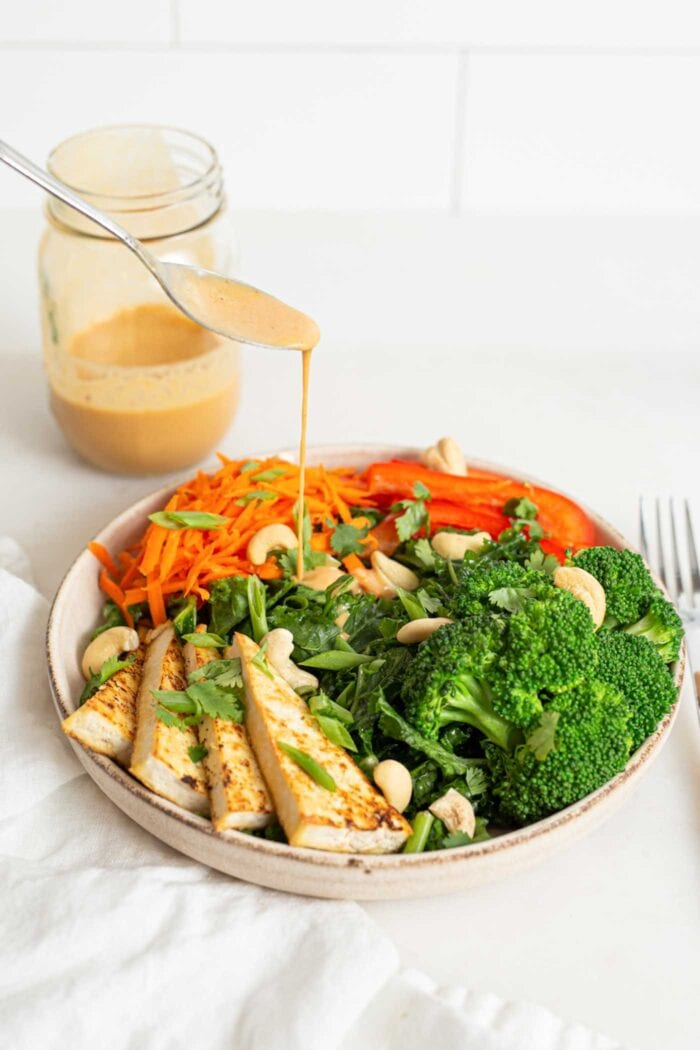 Drizzling a spoonful of dressing over a bowl of tofu, broccoli, bell pepper and carrots,
