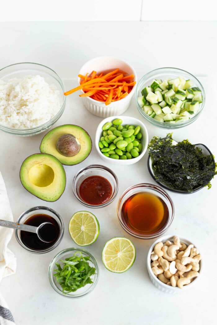 Various ingredients for making sushi in small dishes on a kitchen counter.