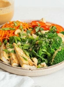 A bowl of tofu and fresh veggies on a counter with a jar of sauce in background.