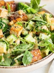 A bowl of salad with arugula, avocado, cucumber, tofu and tempeh. Slice of lemon in background.