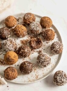 Plate of chocolate no-bake energy balls rolled in coconut, one has a bite out of it.