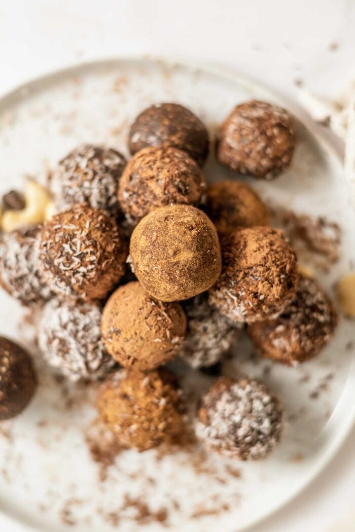 Plate full of no-bake chocolate balls coated in cocoa and coconut.