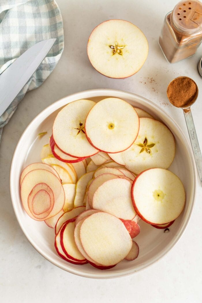 Overhead image of a bowl of thinly sliced apples.