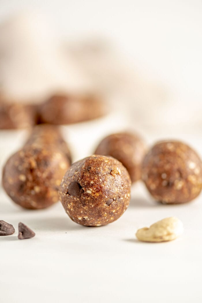 Close up of a cookie dough ball. More balls in background. Cashews and chocolate chips scattered in foreground.