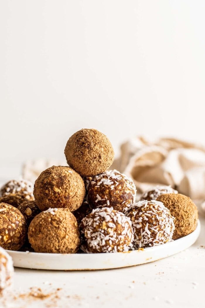 Stack of energy balls coated in coconut or cinnamon sugar on a plate.