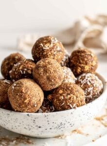 Bowl full of energy balls. Some are coated in cinnamon or coconut.
