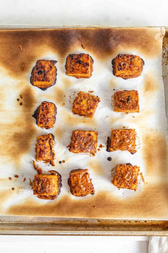 Baked tempeh on a baking tray lined with parchment paper.