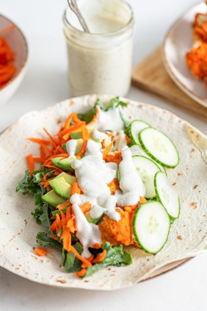 Cucumber, avocado, buffalo cauliflower, carrot and a creamy sauce in an open tortilla wrap.