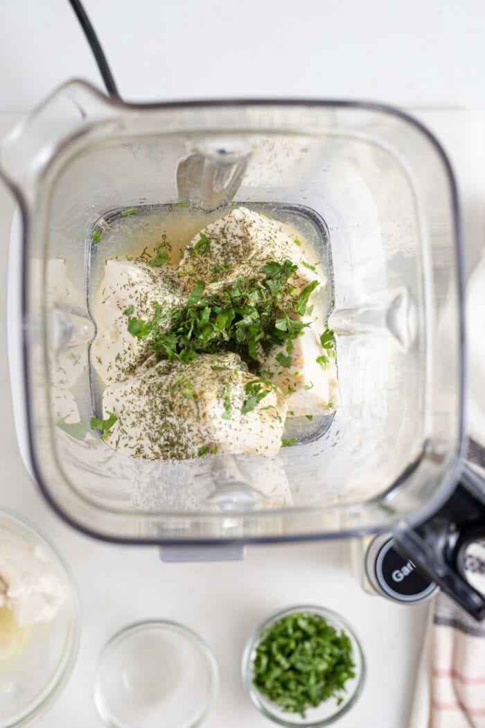 Tofu and parsley in a blender shown from overhead.