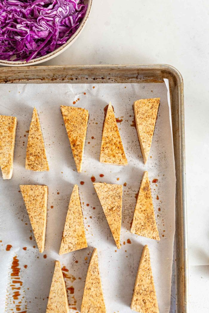 Sliced triangles of tofu with sauce on them on a baking pan.