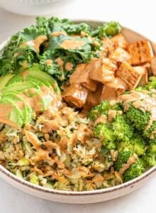 Salad with tofu, cabbage, kale, broccoli, avocado and sauce.