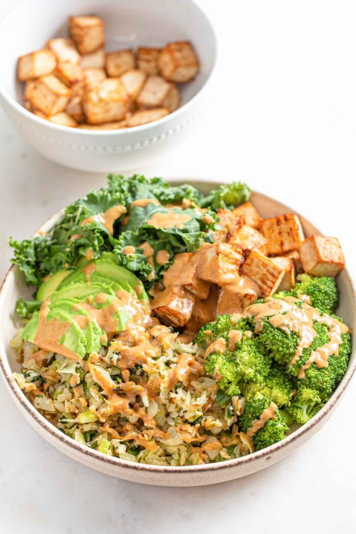 Bowl with cabbage, avocado, tofu, onion, kale and broccoli, topped with sauce.