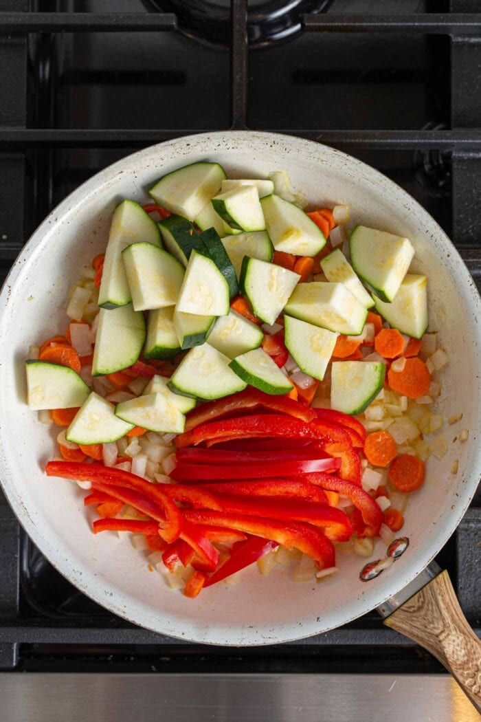 Diced zucchini and thinly sliced bell pepper in a skillet with carrot, onion and garlic.