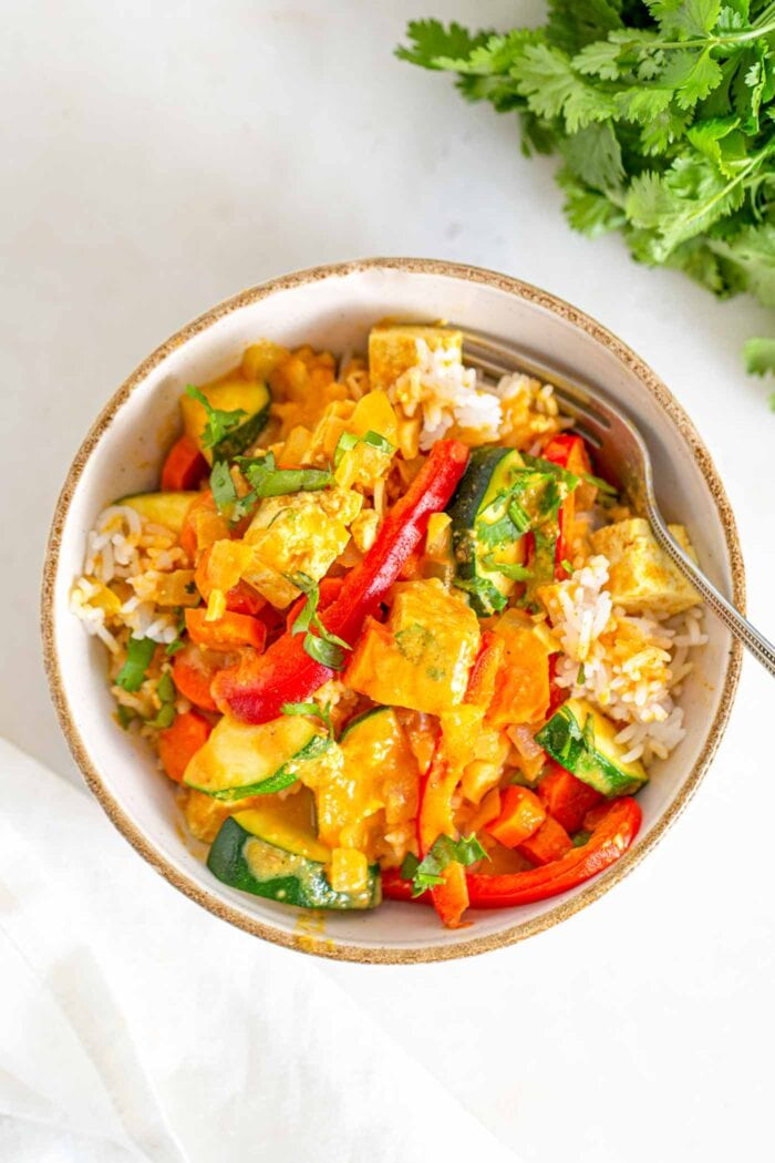 A bowl of tofu vegetable curry over rice with cilantro beside it.
