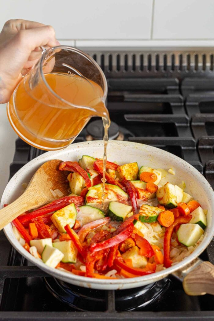 Pouring vegetable broth into a vegetable stir fry cooking in a skillet.