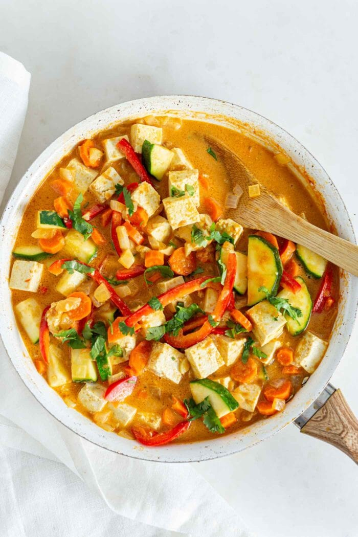 Thick and creamy vegetable curry with tofu in a skillet with a wooden spoon.