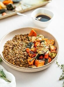 Lentils and roasted vegetables in a bowl. Small dish of balsamic dressing in background.