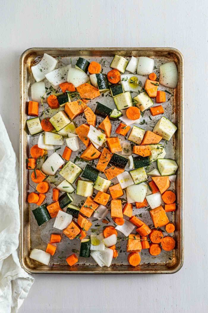 Various chopped root vegetables on a baking tray sprinkled with rosemary and thyme.