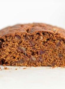 Cut open loaf of pumpkin bread with dates in it.