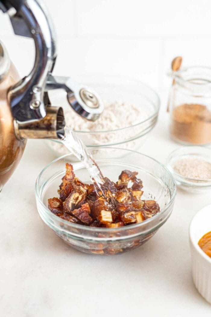 Pouring boiled water over pitted, chopped dates in a bowl.