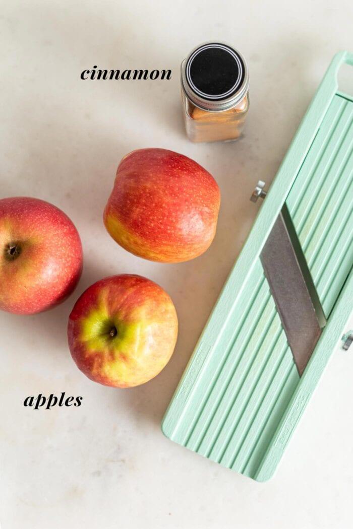 3 apples, mandolin and jar of cinnamon on a counter.