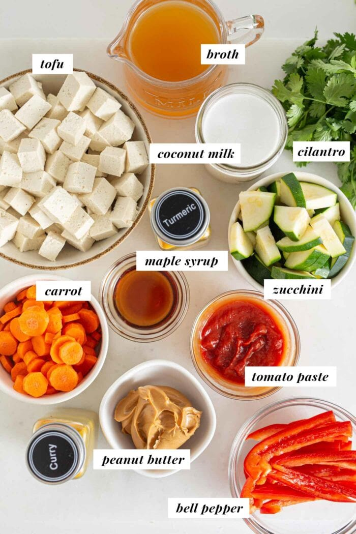Labelled ingredients for a vegetable panang curry in bowls on a counter top.