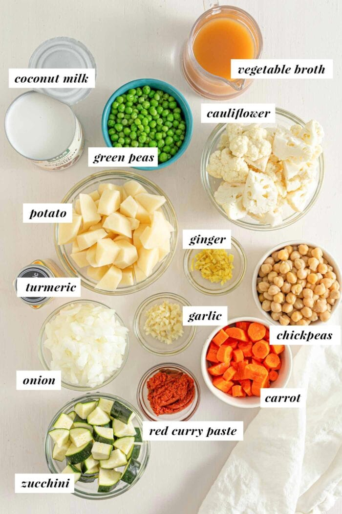 Labelled ingredients for making chickpea potato stew with curry paste and green peas.