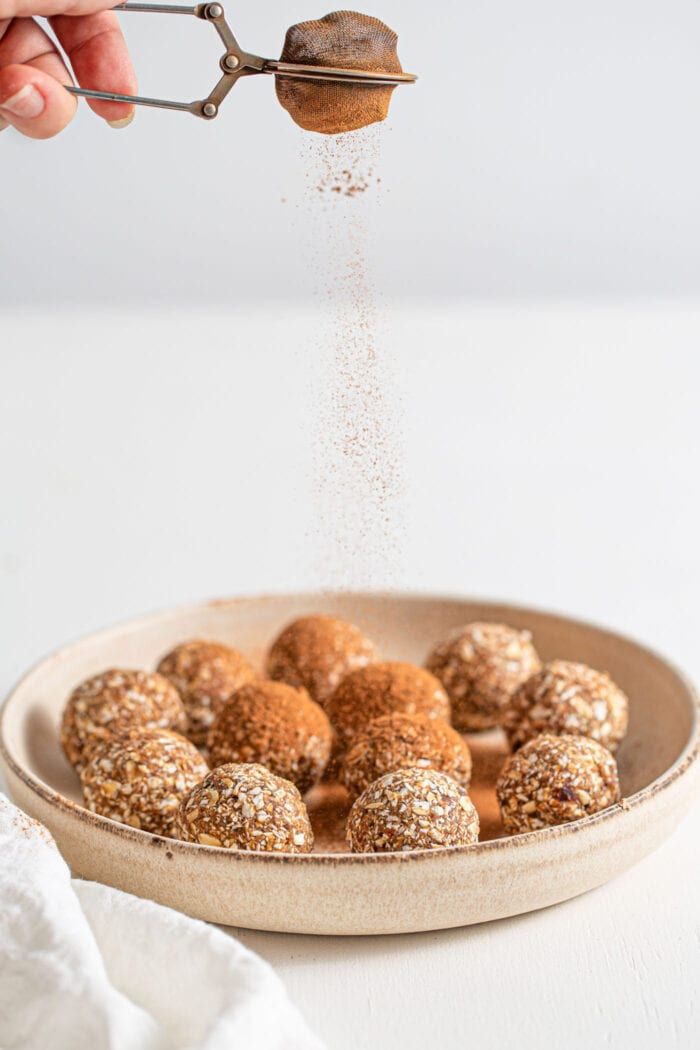 Sprinkling a plate of energy balls with cinnamon.