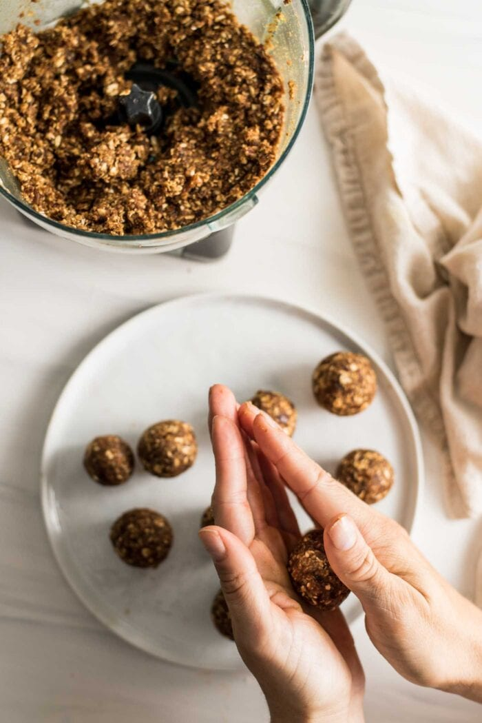 Two hands rolling dough into energy balls. Plate of balls underneath the hands.