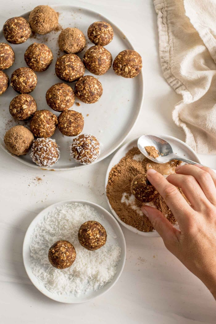 Hand rolling an energy ball in coconut sugar on a small plate. Plate of balls beside it.
