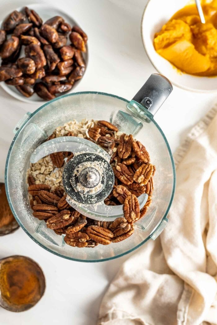 Pecans and oats in a food processor. Bowls of pumpkin and dates beside it.
