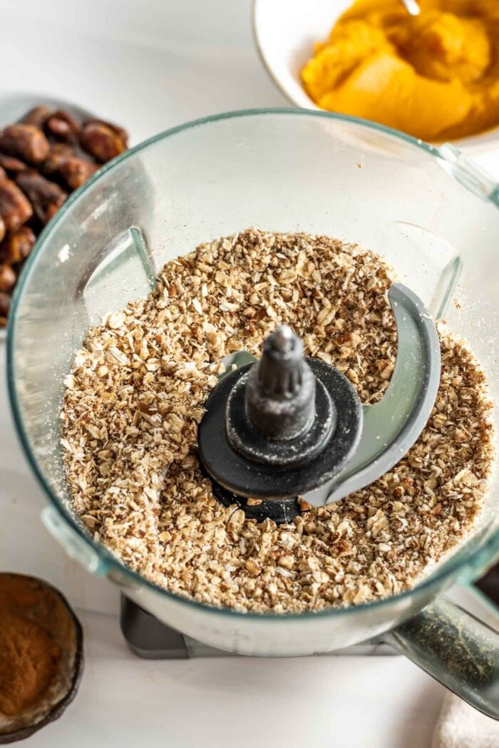 Blended up pecans and oats in a food processor. Bowls of dates and pumpkin beside it.