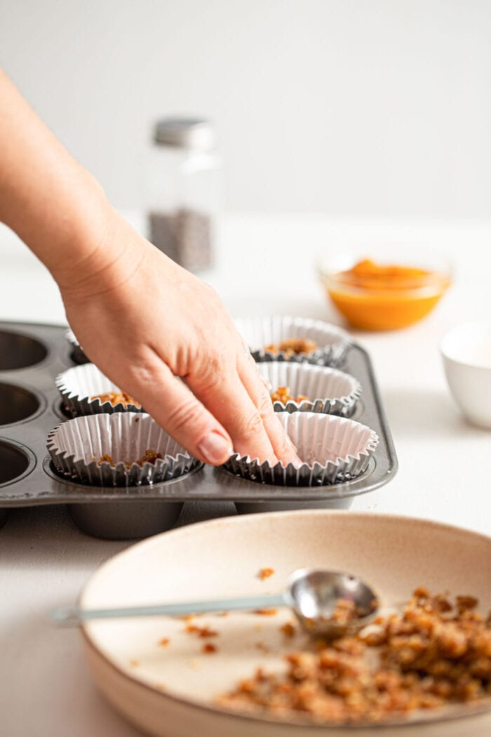 Hand pressing dough into a lined muffin tin.