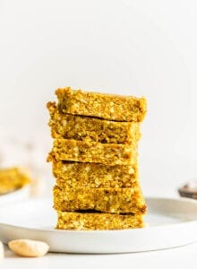 Stack of 6 turmeric coconut and cashew energy bars on a small plate.