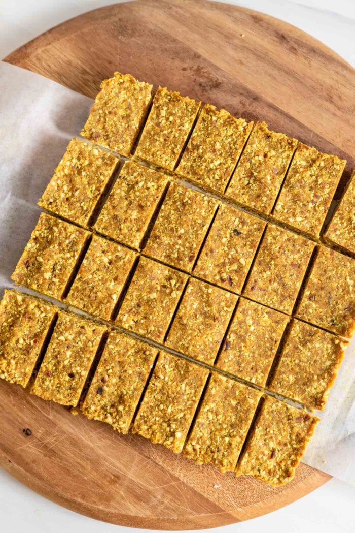 24 slices of small energy bars sitting on parchment on a cutting board.