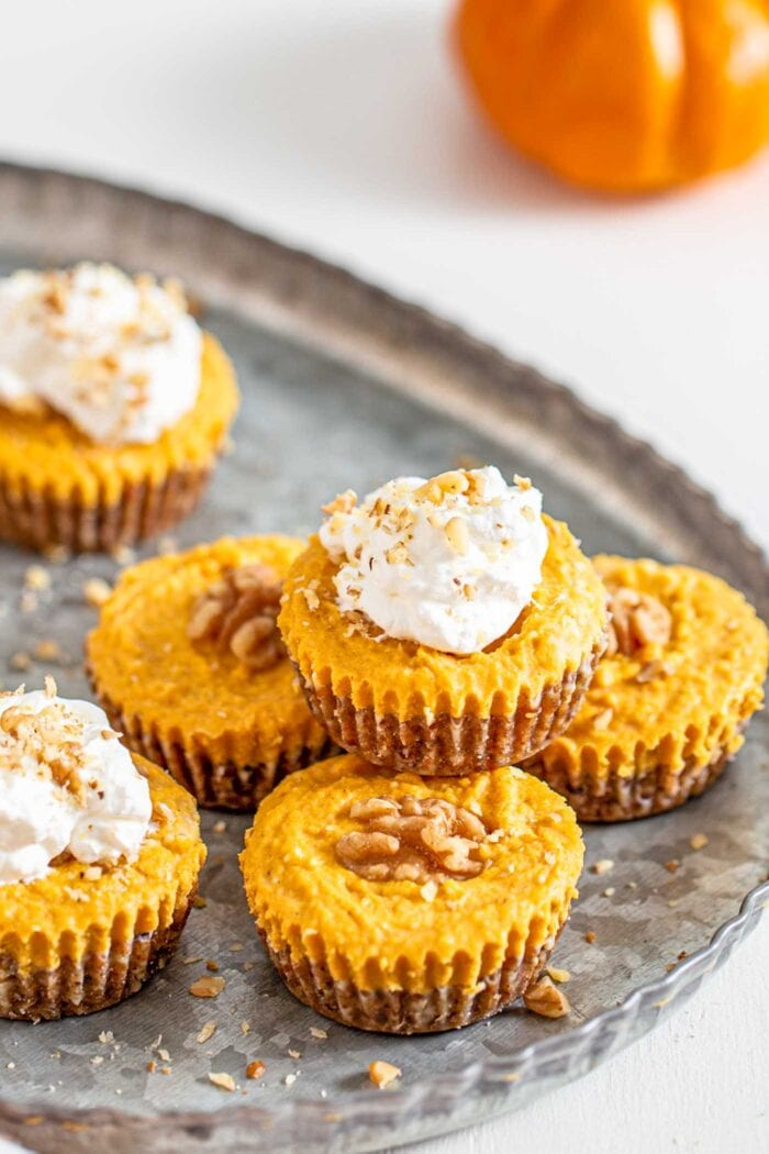 6 pumpkin tarts on a baking tray. Some topped with whipped cream.